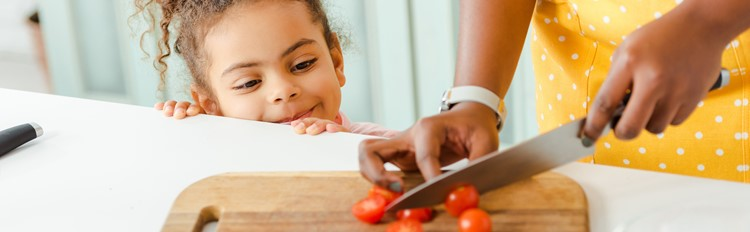 Chopping up tomatoes, child looks on